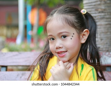 Face of Asian child girl with makeup and sticking on face sequins in the form of stars.