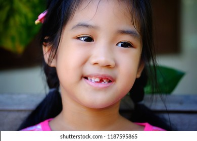 The face of asian girl, black long hair and bright smiling  show the missing teeth.