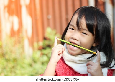 Face Asian girls She is playing a cute pencil.