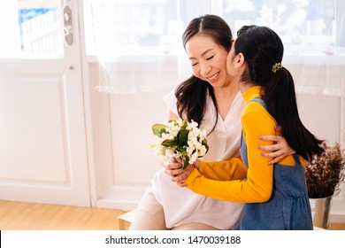 Face of Asian teenage daughter hugging and kissing happy smiling middle-aged mother with tenderness in indoor living room at home. Mother is holding a bouquet received from child. Mother's day concept