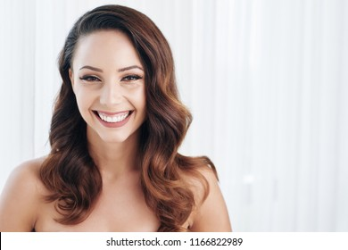 Face of attractive smiling young woman smiling and looking at camera