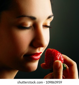 Face of attractive woman smelling strawberry with closed eyes