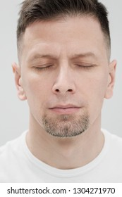 The face of a bearded brunet man in white clothes, eyes closed close up. Smooth skin, beautiful features.