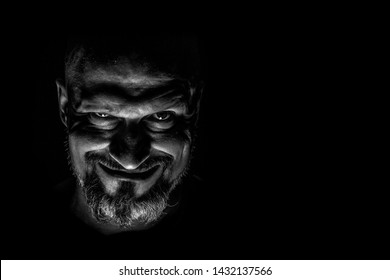 Face with a bearded man grimace against a dark background with sharp shadows. Comedic, fabulous villain or negative character conception with copy space.