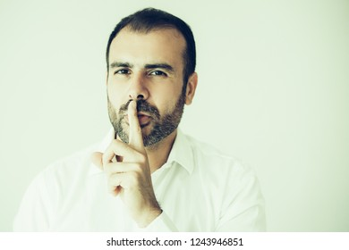 Face of bearded man wearing white shirt with finger on lips. Portrait of mid adult Caucasian businessman showing silence gesture. Silence and secrecy concept