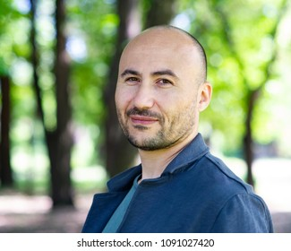 face of a bearded smiling bald man in the park. Portrait of a middle-aged man.