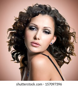 Face of  beautiful adult woman with curly hairs over brown background