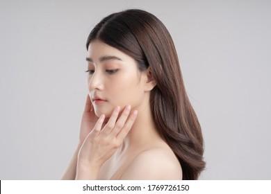 Das Gesicht einer schönen asiatischen Frau Sie berührt ihre Wangen