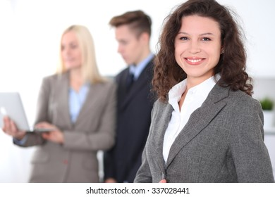 Face of a beautiful cheerful smiling business woman on the background of colleagues