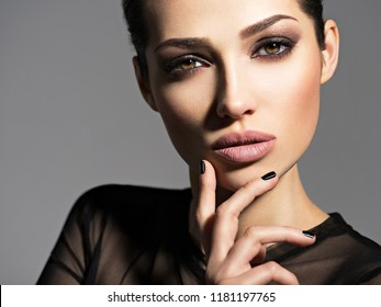 Face of a beautiful girl with smoky eyes makeup posing at studio over dark background