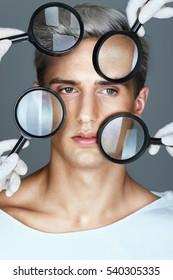 Face of beautiful man with magnifiers. Concept of rejuvenation and skin care.