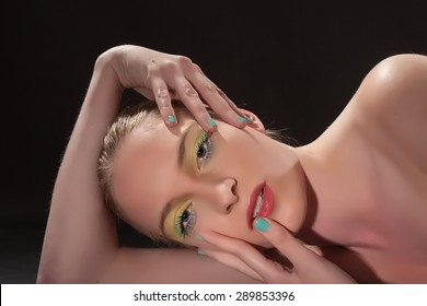 Face of a beautiful sensual woman , with mint-green fingernails at the lips and forehead / Beautiful sensual woman