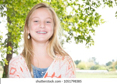 face of a beautiful teenager blonde girl with dental braces on a sunny day