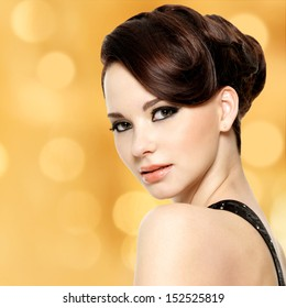 Face of beautiful woman with fashion hairstyle and glamour makeup - over creative soft bokeh background