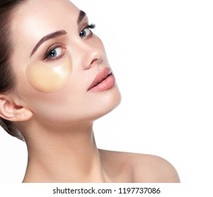 Face of beautiful woman with fresh daily make-up applying lift eye patches. Patches moisturizing and refreshing the skin under the eyes