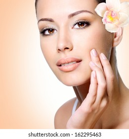 Face of beautiful woman with health skin and  flower over art background