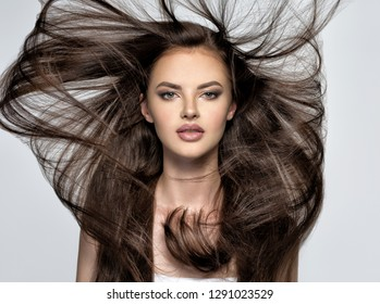 Face of the beautiful woman with long brown  hair posing at studio