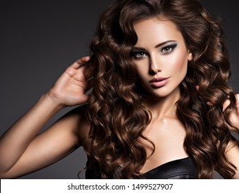 Face of the beautiful woman with long brown curly hair posing at studio over dark background