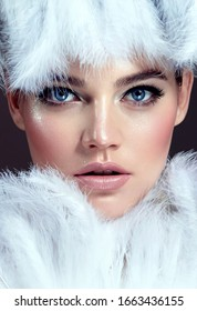The face of a beautiful young blue-eyed girl with smooth skin surrounded by white fluffy feathers