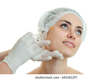 the face of a beautiful young girl in medical CAP which the doctor looks up and smiles makes her prick close-up