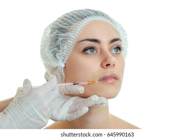 the face of a beautiful young girl in medical Cap where the beautician enters injection close-up