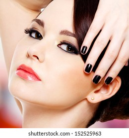 Face of the beautiful young woman with black nails looking at camera