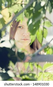 The face of a beautiful young woman in a green summer foliage on a sunny day