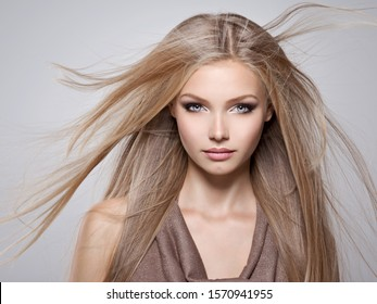Face of the Beautiful young woman with long straight  hair - posing at studio over gray background