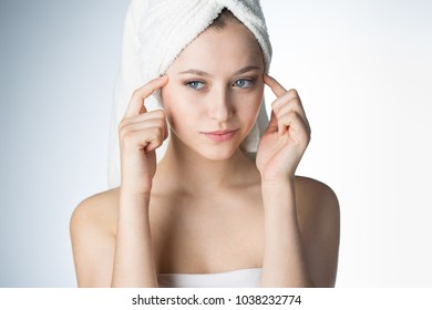 Face of a beautiful young woman with a towel on a white background