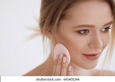 Face Beauty. Closeup Glamorous Girl Using Cosmetic Puff Putting Dry Foundation, Powder On Facial Skin. Portrait Of Beautiful Woman With Natural Makeup And Healthy Soft Skin. Cosmetics. High Resolution