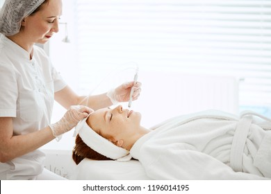 Face Beauty Treatment. Close up of female client getting facial gas-liquid oxygen water epidermal peeling using hardware apparatus