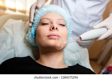 Face Beauty Treatment. Woman Getting Facial Darsonval Therapy Using High Frequency D'Arsonval, Skin Care Device For Anti Spot An