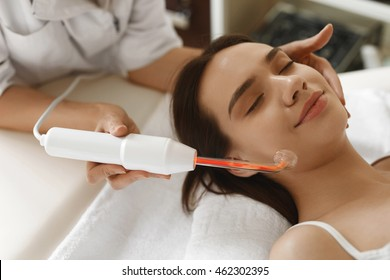 Face Beauty Treatment. Woman Getting Facial Darsonval Therapy Using High Frequency D'Arsonval, Skin Care Device For Anti Spot And Acne Treatment At Cosmetology Center. High Resolution Image