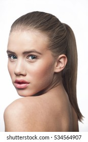 Face of a blond young woman teenager green eyes ponytail