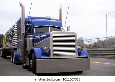 Face of blue American classic popular powerful big rig semi truck tractor with huge grille with flat bed trailer going on the road for delivery commercial cargo to destination warehouse