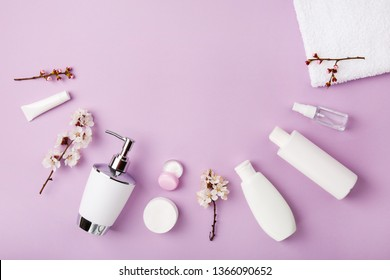 Face and body care products with spring bloom (tonic or lotion, serum, cream, shampoo, micellar water, cotton pads and sticks, shaver) on purple. Freshness and body care. Skin cosmetics. Border banner