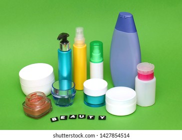 Face, body and hair beauty products packages on green background