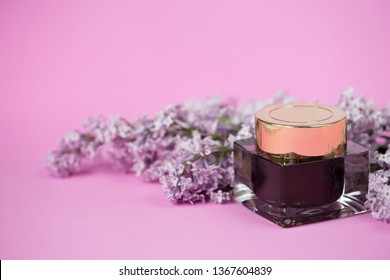Face and body skin care. Glass black jar of cosmetic cream with a gold lid on a pink background with sprigs of lilac flowers. Spa treatments at home. black mask