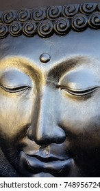 Face of buddha in reflective grey paint