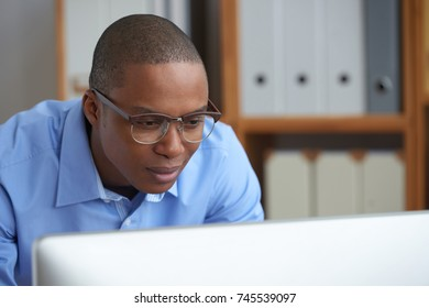 Face of businessman reading information on computer monitor