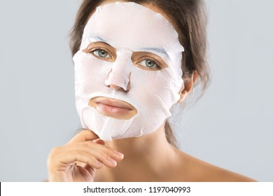 Face care and beauty treatments. Woman with a sheet moisturizing mask on her face isolated on gray background