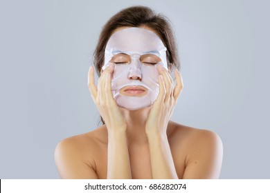 Face care and beauty treatments. Woman with a cloth moisturizing mask on her face isolated on gray background