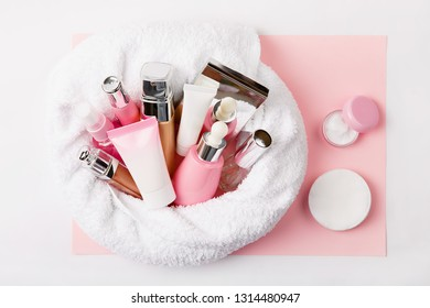 Face care and  make up products (tonic or lotion, serum, cream, micellar water, cotton pads, consealer, mirror) covered in towel on pink, powder background. Freshness and face care. Female cosmetics.