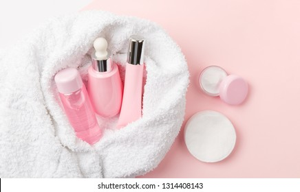 Face care products (tonic or lotion, serum, cream, micellar water, cotton pads) covered in towel on pink, powder background. Freshness and face care. Skin cleansing and anti-age care. Female cosmetics