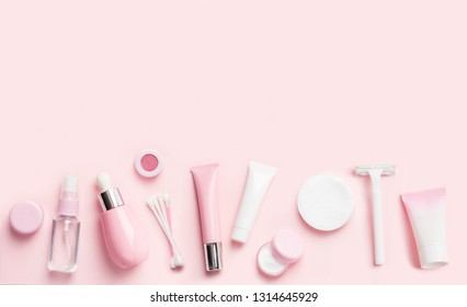 Face care products (tonic or lotion, serum, cream, micellar water, cotton pads and sticks, shaver) on pink background. Freshness and body care. Skin cosmetics and anti-age care. Border banner