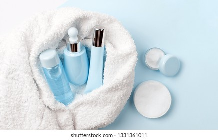 Face care products (tonic or lotion, serum, cream, micellar water, cotton pads) covered in towel on blue, powder background. Freshness and face care. Skin cleansing and anti-age care. Female cosmetics