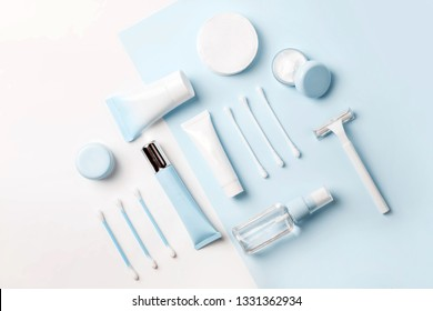 Face care products (tonic or lotion, serum, cream, micellar water, cotton pads and sticks, shaver) on blue background. Freshness and body care. Skin care and anti-age care. Top view rectangle layout