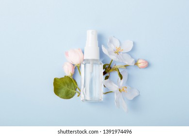 Face care products (tonic or lotion, spray) on blue background with spring apple blossom. Freshness natural anti-age care. Female everyday fresh cosmetics
