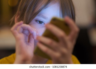The face of the child, illuminated by the phone screen in his hands