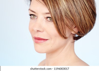Face close up of beautiful middle aged woman with short brown hair, fresh makeup, naked shoulders and neck over white background - mature beauty, skin care or anti age concept